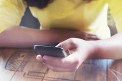 Χέρια γυναικών που χρησιμοποιούν στην έξυπνη τηλεφωνική συνεδρίασή της στον ξύλινο πίνακα σε μια καφετερία Στοκ Εικόνες