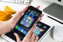 Χέρια γυναικών που χρησιμοποιούν το iphone 7 με τα εικονίδια των κοινωνικών μέσων facebook, instagram, πειραχτήρι, google εφαρμογ Στοκ Φωτογραφίες