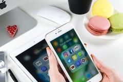 Χέρια γυναικών που χρησιμοποιούν το iphone 7 με τα εικονίδια των κοινωνικών μέσων facebook, instagram, πειραχτήρι, google εφαρμογ Στοκ φωτογραφία με δικαίωμα ελεύθερης χρήσης