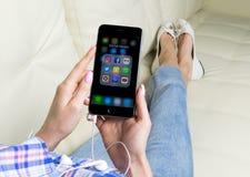 Χέρια γυναικών που χρησιμοποιούν το iphone 7 με τα εικονίδια των κοινωνικών μέσων facebook, instagram, πειραχτήρι, google εφαρμογ Στοκ Εικόνα