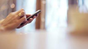 Χέρια γυναικών που, χρησιμοποιώντας το smartphone στον καφέ απόθεμα βίντεο