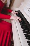 Χέρια γυναικών στο άσπρο πιάνο πληκτρολογίων, παίζοντας μελωδία Μουσική έννοιας Στοκ Εικόνες