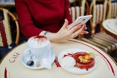 Χέρια γυναικών ` s με το κινητά τηλέφωνο, το φλιτζάνι του καφέ και το κέικ Στοκ Φωτογραφία