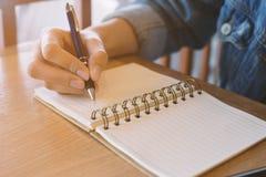 χέρια γυναικών ` s που γράφουν στο σπειροειδές σημειωματάριο που τοποθετείται Στοκ φωτογραφία με δικαίωμα ελεύθερης χρήσης
