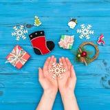 Χέρια γυναικών ` s που κρατούν ξύλινα snowflakes Χριστουγέννων κοντά στα κιβώτια δώρων και το νέο έτος Στοκ φωτογραφίες με δικαίωμα ελεύθερης χρήσης