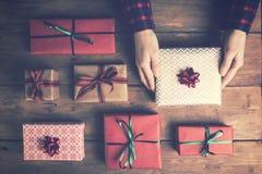 χέρια γυναικών ` s που κρατούν το συσκευασμένο κιβώτιο δώρων στον παλαιό ξύλινο πίνακα Στοκ φωτογραφία με δικαίωμα ελεύθερης χρήσης