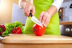 Χέρια γυναικών ` s που κόβουν την ντομάτα Στοκ εικόνες με δικαίωμα ελεύθερης χρήσης