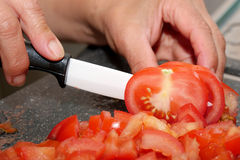 Χέρια γυναικών ` s που κόβουν την ντομάτα Στοκ φωτογραφία με δικαίωμα ελεύθερης χρήσης