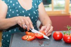 Χέρια γυναικών ` s που κόβουν την ντομάτα Στοκ Εικόνες