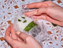 Χέρια γυναικών ` s που μαγειρεύουν το σπιτικό onigiri με ένα πρόσωπο χαμόγελου στοκ εικόνες