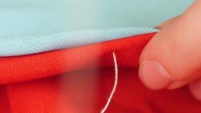 Χέρια γυναικών ` s που ράβουν με τη βελόνα, άσπρο νήμα και φιλμ μικρού μήκους