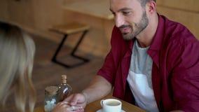 Χέρια εκμετάλλευσης ζεύγους κατά την ημερομηνία στον καφέ απόθεμα βίντεο