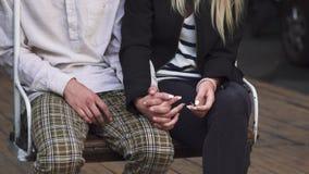 Χέρια εκμετάλλευσης νεαρών άνδρων και γυναικών καθμένος στην ταλάντευση απόθεμα βίντεο
