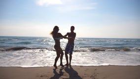 Χέρια εκμετάλλευσης νεαρών άνδρων και γυναικών και περιστροφή στην ακτή Χαρούμενο ζεύγος που στροβιλίζεται γύρω μαζί μια ηλιόλουσ απόθεμα βίντεο