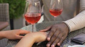 Χέρια εκμετάλλευσης νεαρών άνδρων και γυναικών, χαλαρώνοντας με το κρασί, που φλερτάρει κατά την πρώτη ημερομηνία φιλμ μικρού μήκους