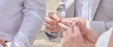 Χέρια εκμετάλλευσης νυφών και νεόνυμφων και ανταλλαγή των δαχτυλιδιών στοκ φωτογραφία