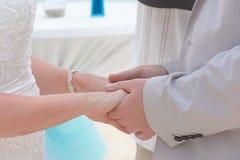 Χέρια εκμετάλλευσης νυφών και νεόνυμφων και ανταλλαγή των δαχτυλιδιών στοκ εικόνες