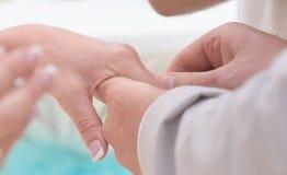 Χέρια εκμετάλλευσης νυφών και νεόνυμφων και ανταλλαγή των δαχτυλιδιών στοκ φωτογραφίες με δικαίωμα ελεύθερης χρήσης