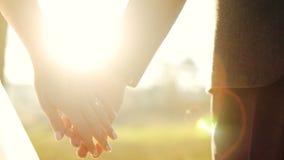 Χέρια εκμετάλλευσης γαμήλιου ζεύγους στο υπόβαθρο ηλιοβασιλέματος που πυροβολείται σε αργή κίνηση στενό σε επάνω απόθεμα βίντεο