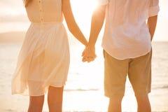 Χέρια εκμετάλλευσης ζεύγους ζεύγους στο ηλιοβασίλεμα στην παραλία στοκ φωτογραφία