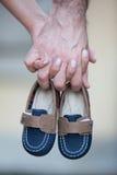 Χέρια εκμετάλλευσης ζεύγους και μικρά παπούτσια στοκ εικόνα