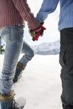 Χέρια εκμετάλλευσης ζεύγους και περπάτημα μέσω του χιονιού Στοκ Φωτογραφία
