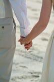 Χέρια εκμετάλλευσης ζεύγους κατά τη διάρκεια μιας γαμήλιας τελετής παραλιών Στοκ Εικόνες