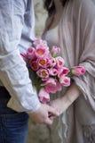 Χέρια εκμετάλλευσης ζεύγους με τα λουλούδια Στοκ Φωτογραφίες
