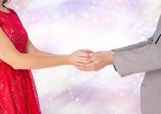 Χέρια εκμετάλλευσης ζεύγους με το λαμπιρίζοντας ελαφρύ υπόβαθρο bokeh Στοκ εικόνα με δικαίωμα ελεύθερης χρήσης