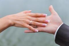 Χέρια εκμετάλλευσης με τα γαμήλια δαχτυλίδια Στοκ Φωτογραφία