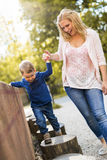 Χέρια εκμετάλλευσης μητέρων με το γιο της και τη βοήθεια τον να περπατήσει Στοκ φωτογραφία με δικαίωμα ελεύθερης χρήσης