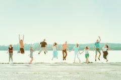Χέρια εκμετάλλευσης ομάδας ανθρώπων και άλμα στο πάρκο κοντά στη λίμνη Χαμογελώντας κορίτσια και αγόρια που έχουν τη διασκέδαση Στοκ εικόνες με δικαίωμα ελεύθερης χρήσης