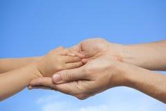 Χέρια εκμετάλλευσης πατέρων και γιων στο υπόβαθρο ουρανού Στοκ εικόνα με δικαίωμα ελεύθερης χρήσης