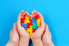 Χέρια ενηλίκων και παιδιών που κρατούν τη ζωηρόχρωμη καρδιά στο μπλε υπόβαθρο Έννοια ημέρας συνειδητοποίησης παγκόσμιου αυτισμού στοκ εικόνες με δικαίωμα ελεύθερης χρήσης