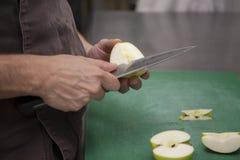 Χέρια ενός αρχιμάγειρα που κόβει ένα μήλο στοκ φωτογραφία με δικαίωμα ελεύθερης χρήσης