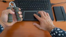 Χέρια ενός ατόμου χρησιμοποιώντας το lap-top και ασκώντας με το ελατήριο-πιάσιμο στη θέση γραφείων, στο γραφείο στοκ εικόνα