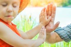 Χέρια ενός γονέα και ενός παιδιού στη φύση σε ένα πάρκο θαλασσίως στοκ φωτογραφίες