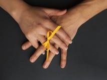 Χέρια ενός ζεύγους ερωτευμένου Δάχτυλα που δένονται από ένα κίτρινο τόξο στοκ εικόνα