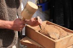 Χέρια ενός λιθοδόμου με το σφυρί και της σμίλης στην εργασία Στοκ Φωτογραφίες