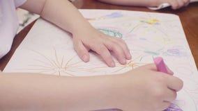 Χέρια ενός μικρού σχεδίου κοριτσιών σε έναν πίνακα φιλμ μικρού μήκους