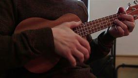 Χέρια ενός νέου τύπου που παίζει το ukulele φιλμ μικρού μήκους
