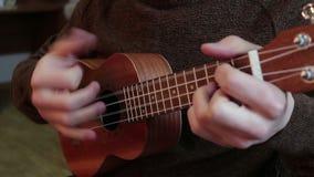 Χέρια ενός νέου τύπου που παίζει το ukulele απόθεμα βίντεο
