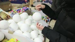 Χέρια ενός προσώπου που επιλέγει τις πολύχρωμες σφαίρες για το χριστουγεννιάτικο δέντρο στην αγορά Μια γυναίκα ζωηρόχρωμος απόθεμα βίντεο