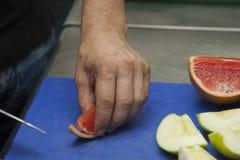 Χέρια ενός τέμνοντος αρχιμάγειρα γκρέιπφρουτ στοκ εικόνες με δικαίωμα ελεύθερης χρήσης