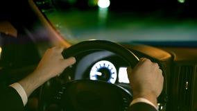 Χέρια ενός unrecognizable νέου επιχειρηματία που οδηγεί το αυτοκίνητό του σε μια πόλη νύχτας απόθεμα βίντεο