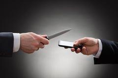 Χέρια επιχειρηματιών με το μαχαίρι και το κινητό τηλέφωνο Στοκ φωτογραφίες με δικαίωμα ελεύθερης χρήσης