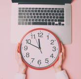 Χέρια επιχειρηματιών με το σημειωματάριο και το μεγάλο ρολόι Στοκ Εικόνα