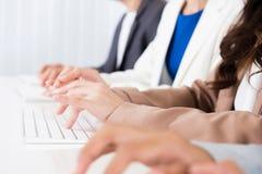 Χέρια επιχειρηματιών που δακτυλογραφούν στα πληκτρολόγια υπολογιστών Στοκ Εικόνες