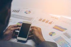 Χέρια επιχειρηματιών που λειτουργούν με ένα smartphone στον άσπρο πίνακα β Στοκ Εικόνες