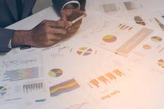 Χέρια επιχειρηματιών που λειτουργούν με ένα smartphone στον άσπρο πίνακα β Στοκ Εικόνα